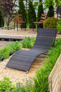 A place to relaxation at backyard in garden: lounge chair, wooden chairs, flowerbed and beautiful trees and shrubs.
