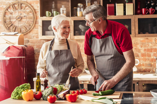 Happy senior couple cooking together on kitchen