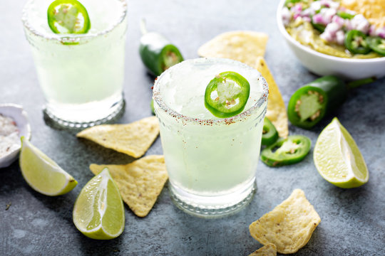Salted rim spicy iced margarita with jalapeno, limes and chips
