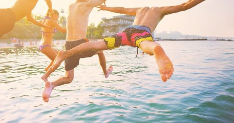 Group of happy crazy people having fun jumping in the sea water from boat. Friends jump in mid air on sunny day summer pool party at diving holiday. Travel vacation, friendship, youth holiday concept. Fotomurales