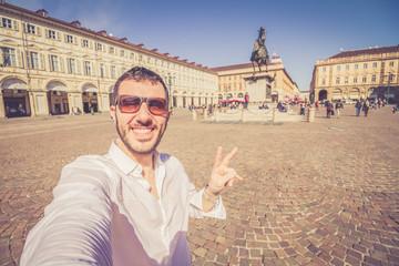 happy man tourist taking selfie photo in Turin Torino city, Piedmont, italy