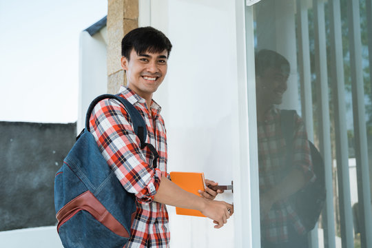 handsome male student lock his room before going to college campus