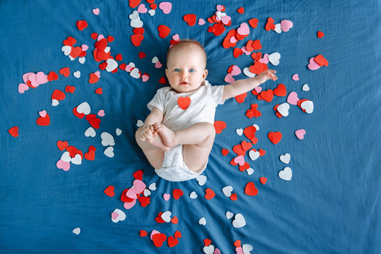 Cute adorable white Caucasian baby girl boy infant with blue eyes four months old lying on bed among many foam paper red pink colorful hearts. View from top above. Happy Valentine day holiday