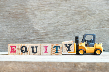 Toy forklift hold letter block y to complete word equity on wood background