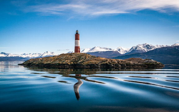 The lighthouse at world's end. Island with lighthouse on a peaceful lake, snowy mountains landscape on a perfect weather day.