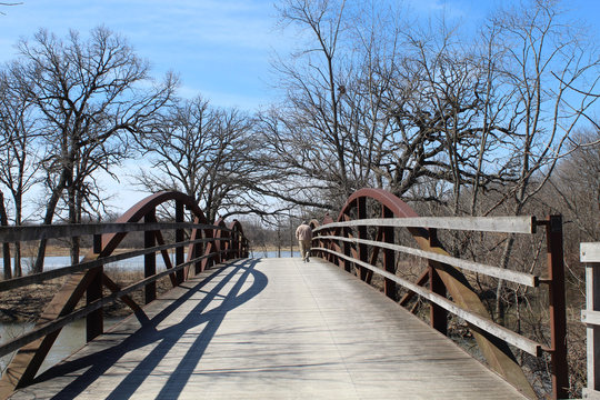 Man walking on an arch bridge at the Independence Grove Forest Preserve in Libertyville, Illinois