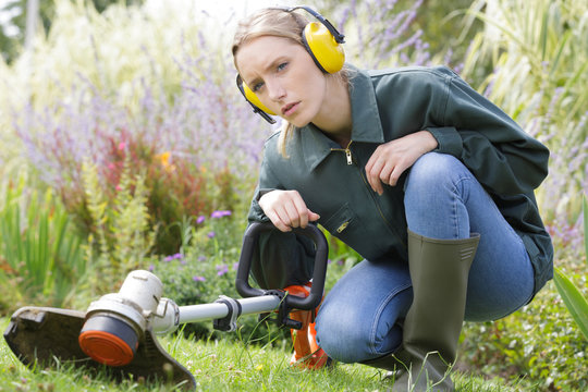 woman crouching down by garden strimmer