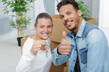 young couple showing keys to their apartment