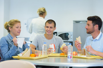 adults sat around table eating packed lunches off of trays