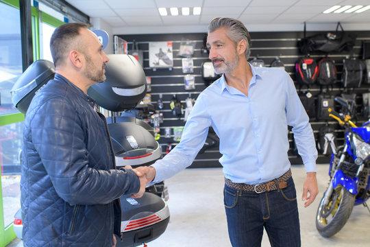motorcycle dealer shaking hands with customer entering shop