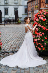 bride stands on the street against the background of pink rose bushes