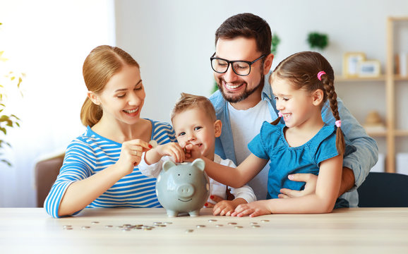 financial planning   family mother father and children with piggy Bank at home.