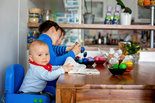 Three children, brothers, coloring and painting easter eggs at home in kitchen