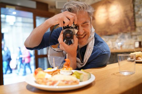 Mature photographer taking photos of tapas plate in Spanish restaurant
