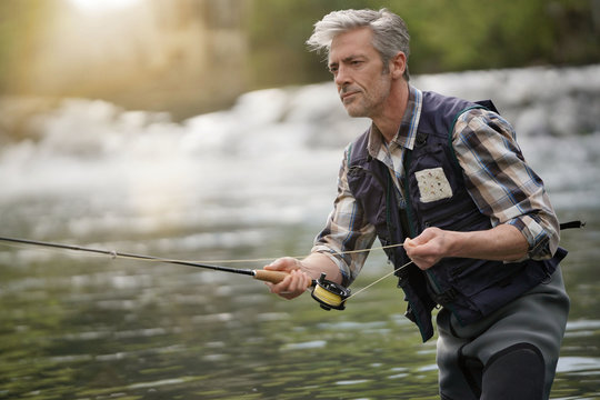 Mature man fly fishing in beautiful river