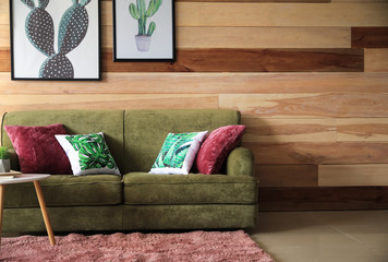 Soft couch near wooden wall in interior of living room