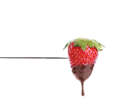 Fondue stick with chocolate covered strawberry on white background
