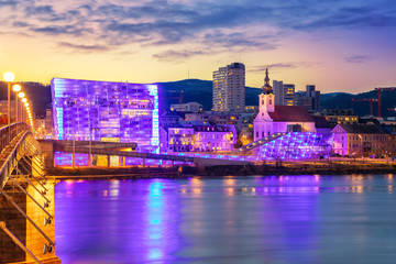 Fototapete - Linz, Austria. Cityscape image of riverside Linz, Austria during twilight blue hour with reflection of the city lights in Danube river.