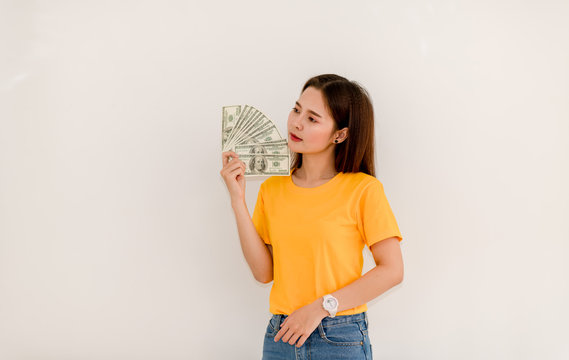 Beautiful Asian girl holding money separately on white background Asian Girls Counting Dollars Save Salaries Succeeded in financial business