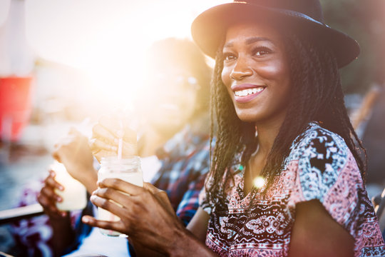Sexy black woman drinking cocktail in summer and enjoying her vacation