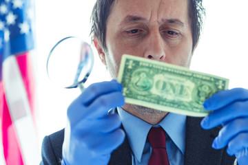 American secret service agent analyzing suspicious counterfeit dollar bill