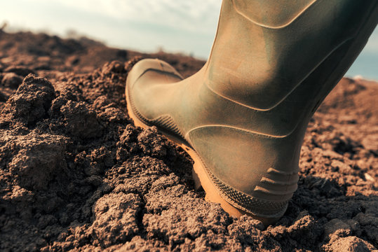 Farmer in wellington rubber boots making first step in field