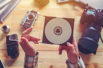 Fototapeta Photographer holding dvd disc with archived photos obraz