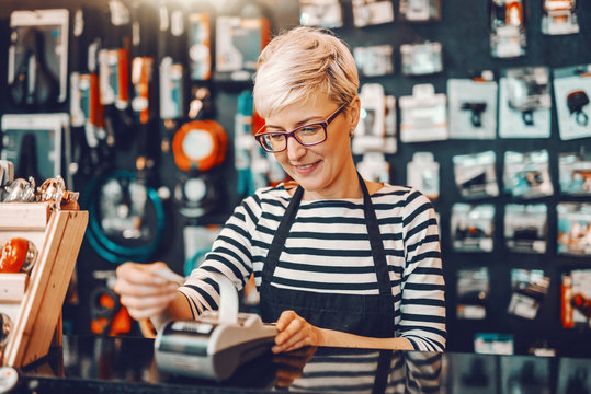 Smiling Caucasian female worker with short blonde hair and eyeglasses using cash register while standing in bicycle store.