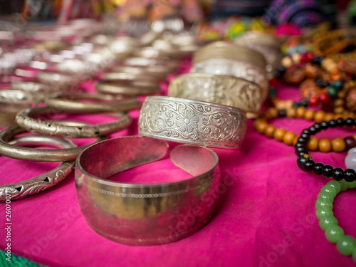 47f30b922 Cheap gift souvenir jewelry on market table in a raw including bracelets  and necklace, shallow