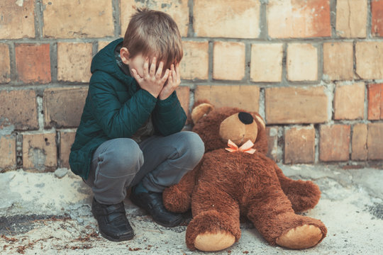 A little boy is crying over a teddy bear outside.