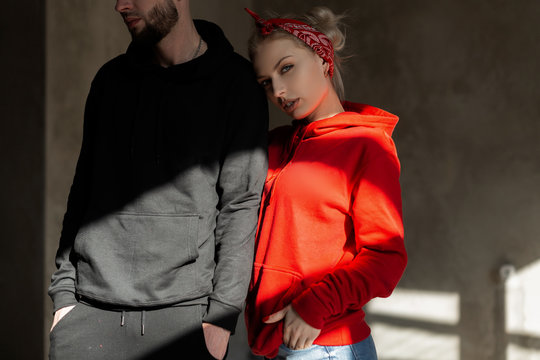 Beautiful young stylish couple in trendy hoodie indoors with sunshine. Hipster girl in red hoodie and handsome man with beard in blue hoodie in studio