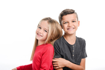 portrait of two young kids boy and girl sibling in studio shot on white background