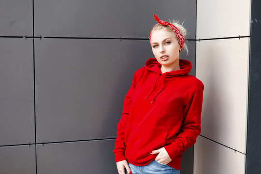 Beautiful pretty stylish young woman with a fashionable hairstyle with a stylish red bandana in a trendy red hooded hoodie in jeans stands near a gray modern building. Attractive girl fashion model.