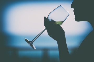 Silhouette image of a woman holding a wine glass to drink with blurred sea background