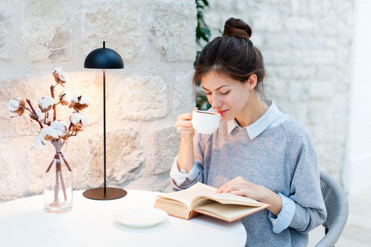 Young woman is drinking coffee and reading book under warm table lamp light. Girl is sitting in cozy modern cafe indoors.