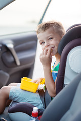 Happy little boy in the car eating cookies