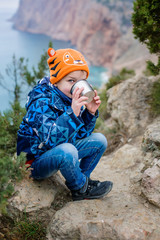 little happy boy is drinking from a thermos on a walk in the mountains by the sea