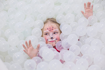 Happy little girl in a playroom in a white room with aqua make-up on her face