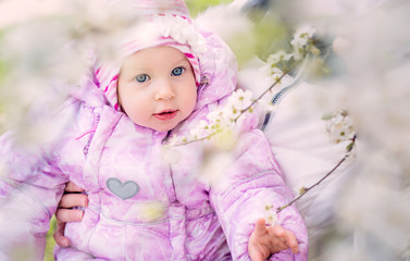 portrait of a beautiful blue-eyed baby 9 months near a flowering tree