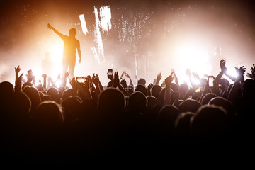Rock concert. Leader on the stage. Silhouette of the crowd in front of the stage.