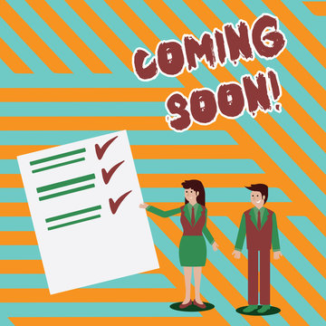 Writing note showing Coming Soon. Business concept for event or action that will happen after really short time Man and Woman Presenting Report of Check and Lines on Paper