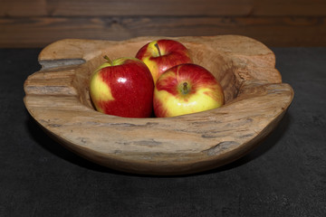 Close-up of Three apples in a wooden bowl