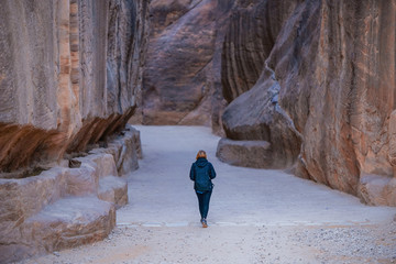 girl goes through a narrow passage in the al-Siq canyon in the mountains leading to the ancient Nabatian city of Petra