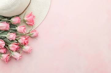 Beautiful flat lay. Pink roses on pastel pink background flat lay. top view of flowers and hat with space for text. Banner mockup with a copy space