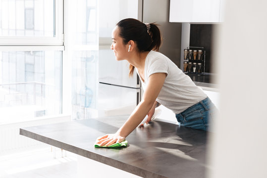 Portrait of charming asian girl cleaning table with detergent and rag in kitchen at home
