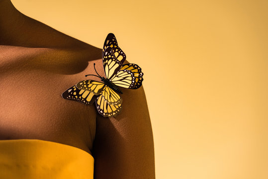 Cropped view of african american woman with butterfly on shoulder on orange