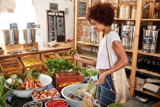 Woman Buying Fresh Fruit And Vegetables In Sustainable Plastic Free Grocery Store