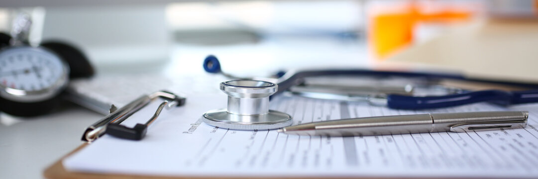 Stethoscope head and silver pen lying on medical application form