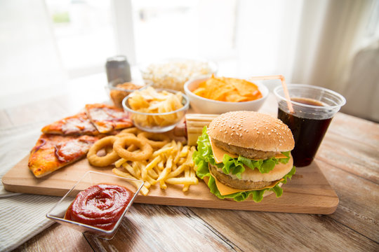fast food and unhealthy eating concept - close up of double hamburger or cheeseburger, deep-fried squid rings, french fries, pizza and cola drink on wooden board
