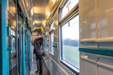 Motion blurred figure of conductor in the wagon of express train. The interior of moving train with long corridor and doors and windows.